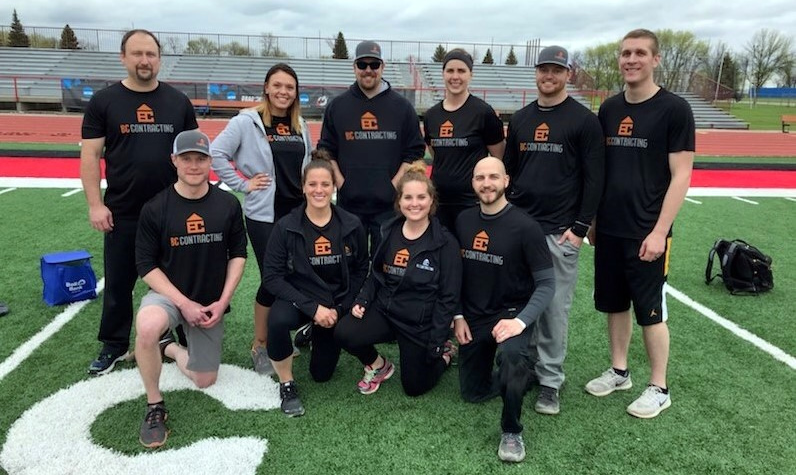 10 BC Contracting team members wearing matching black t-shirts posing for a picture on a football field
